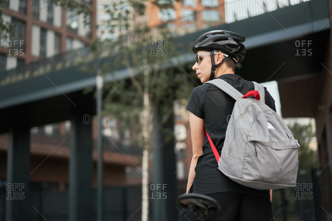 Woman cyclist with backpack outdoors on summer day, back view