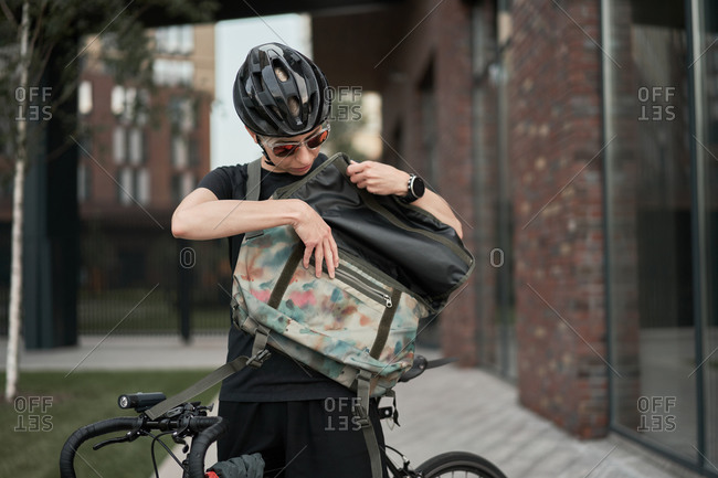 Female courier with bag in his hands on street on summer day