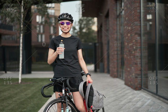 Female cyclist courier with bottle in his hands on street on summer day