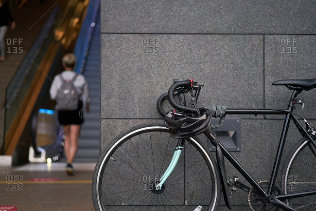 Bicycle standing near building on blurry background of walking woman in afternoon