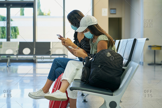 Side view of women in medical masks browsing internet on mobile phones while waiting for flight in airport hall
