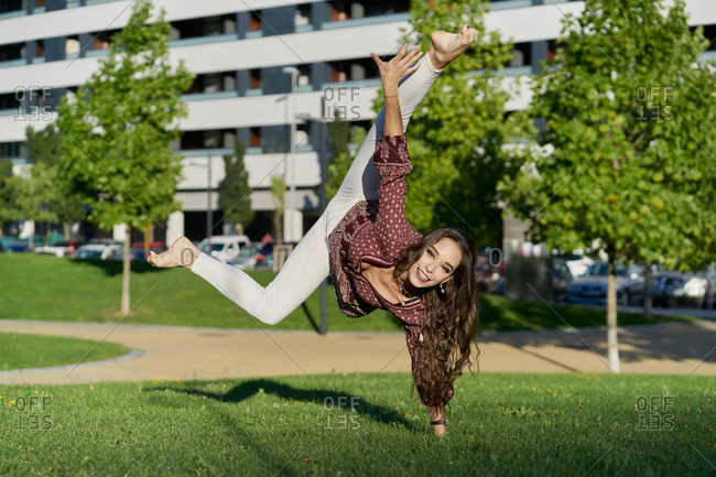 Cheerful young ethnic female dancer demonstrating trick on meadow while standing on hand with raised legs and looking at camera