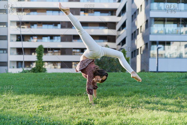 Cheerful young female dancer on meadow while doing handstand looking at camera