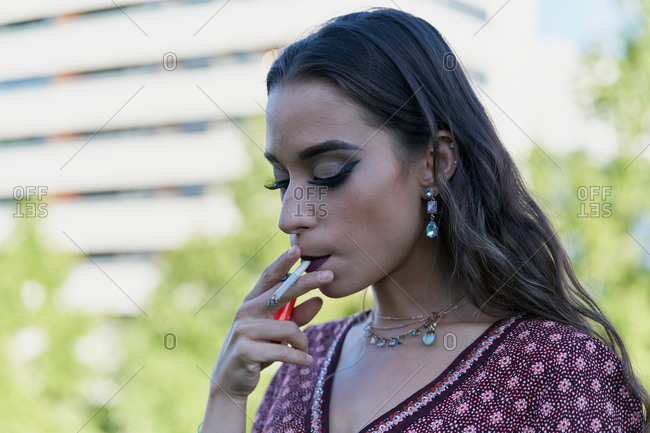 Young trendy ethnic female with makeup in accessories smoking cigarette in the street