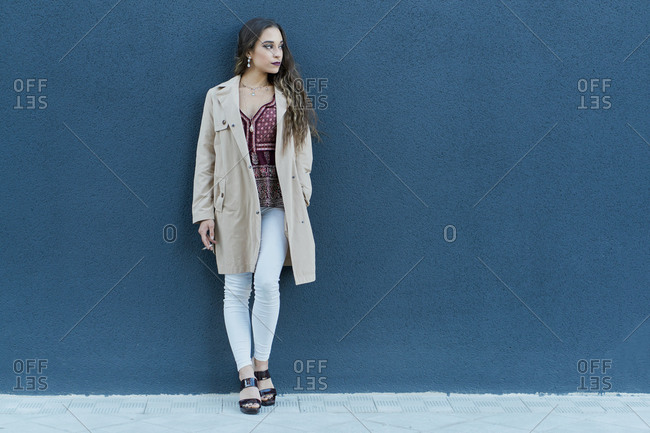 Young pondering ethnic lady in trendy apparel standing with cigarette on pavement near city wall and looking away