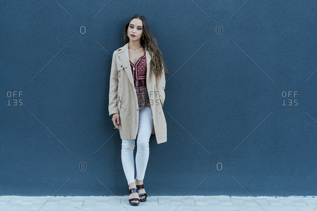 Young pondering ethnic lady in trendy apparel standing with cigarette on pavement near city wall and looking at camera