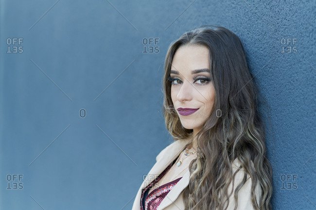 Side view of young pondering ethnic lady in trendy apparel standing on pavement near city blue wall and looking at camera