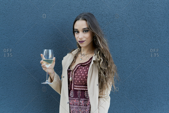 Young smiling female in stylish wear with ornament and makeup standing with glass of white wine while looking at camera