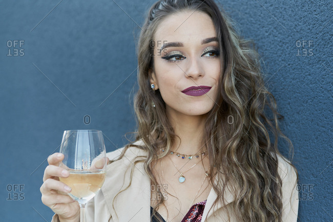 Young woman in stylish wear with ornament and makeup standing with glass of white wine while looking away