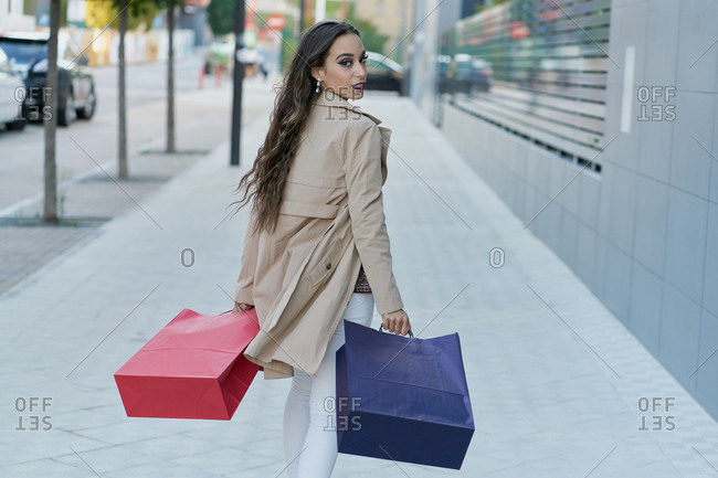 Young content trendy female shopaholic with shopping bags strolling on sidewalk while looking over the shoulder