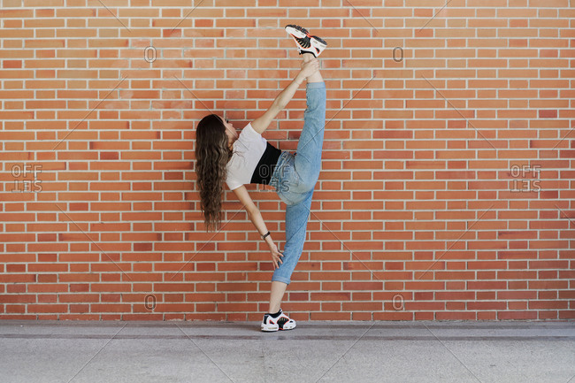 Full body back view of young slim female in trendy casual outfit performing standing split against brick wall