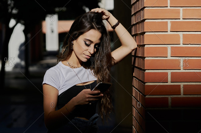 Stylish millennial brunette in casual outfit standing near brick column and using mobile phone on urban street