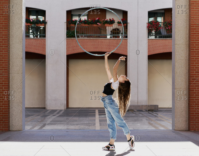 Full body side view of long haired slim female in trendy casual wear performing dance movement with hula hoop on paved square against urban building with columns
