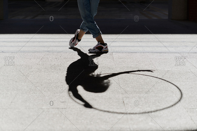 Crop legs and shadow of anonymous slim female in jeans and sneakers performing dance movements with hula hoop on paved street in sunny day