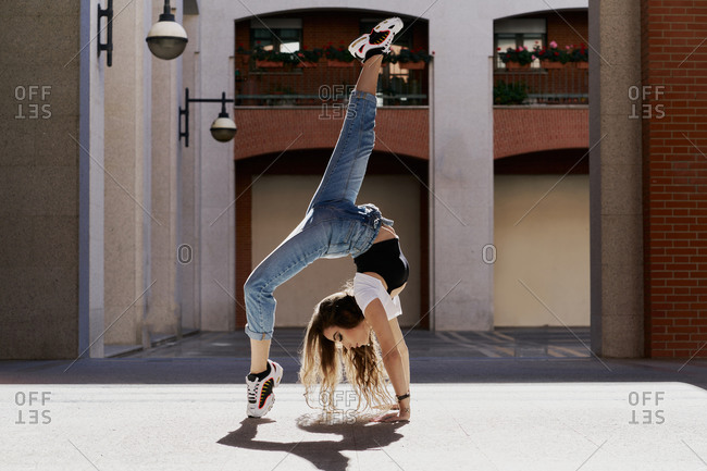 Full body side view of young female dancer in hipster outfit performing Wheel pose on pavement near stone urban building