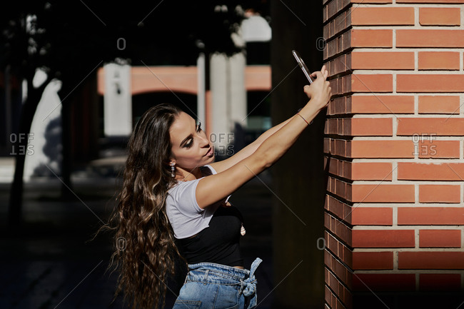 Side view of sensual young long haired brunette in trendy wear taking selfie on mobile phone while standing near brick building on city street