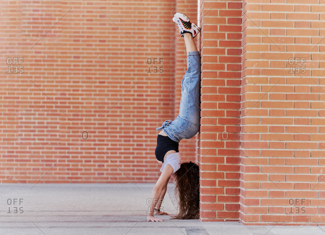 Full body side view of young female dancer in trendy casual outfit performing handstand near brick column on city street