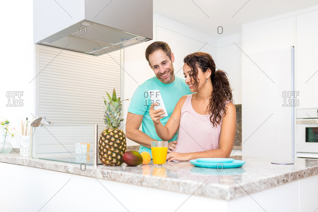 Happy adult man and woman getting good news via mobile phone while standing near kitchen counter with fresh fruits and juice in morning