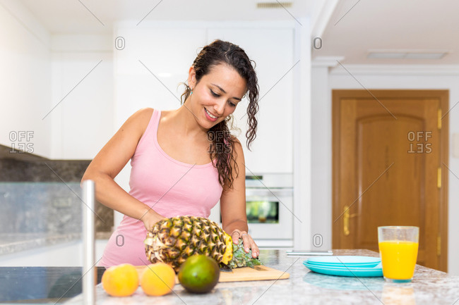 Female cutting ripe pineapple at kitchen counter with fresh fruits while preparing healthy vitamin breakfast at home