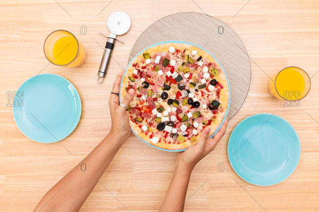 From above crop anonymous female putting plate with delicious homemade pizza on table with glasses of fresh fruit juice while serving lunch at home