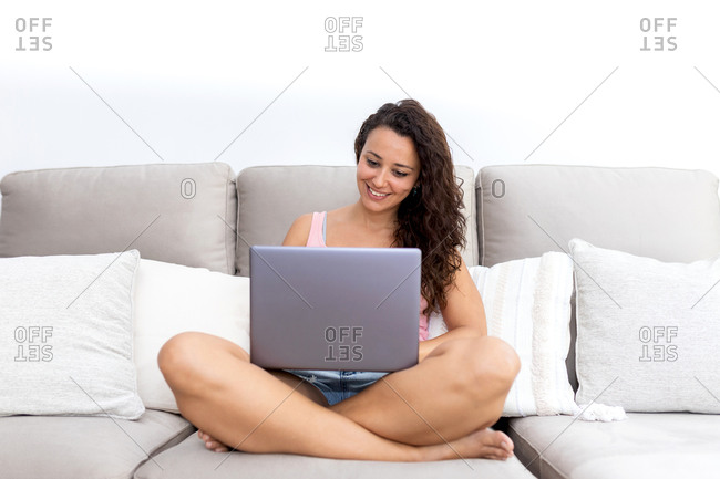 Cheerful young female in casual clothes sitting on comfortable couch and watching video on laptop while chilling at home