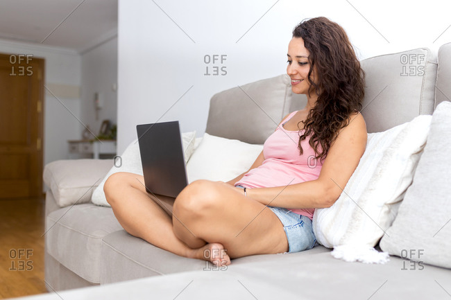 Side view of cheerful young female in casual clothes sitting on comfortable couch and watching video on laptop while chilling at home