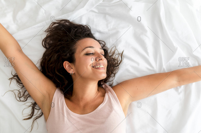 Top view of delighted female lying on bed and stretching after awakening in bedroom in morning
