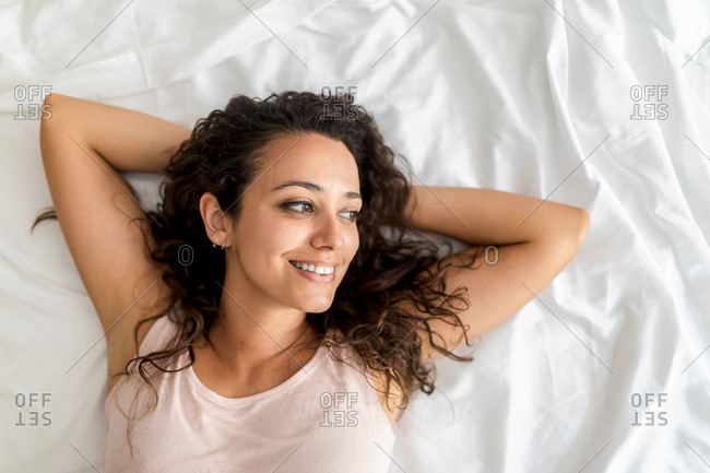 Top view of delighted female lying on bed looking away after awakening in bedroom in morning