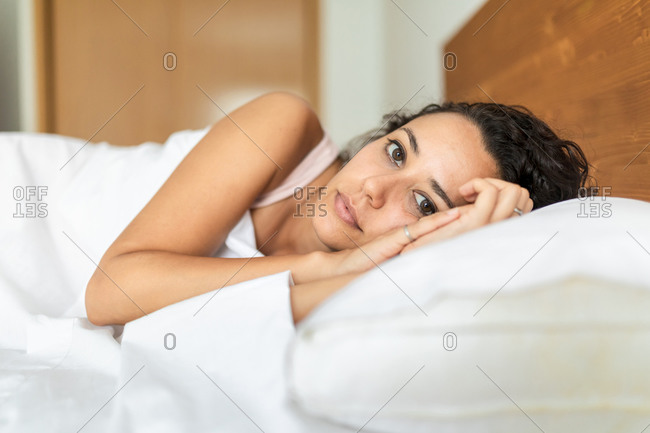 Calm female in pajama lying in bed on soft pillow under white blanket looking at camera