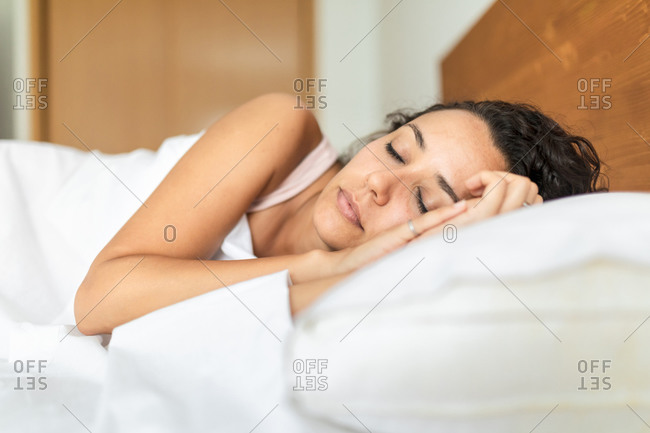 Calm female in pajama lying in bed on soft pillow under white blanket and sweetly sleeping