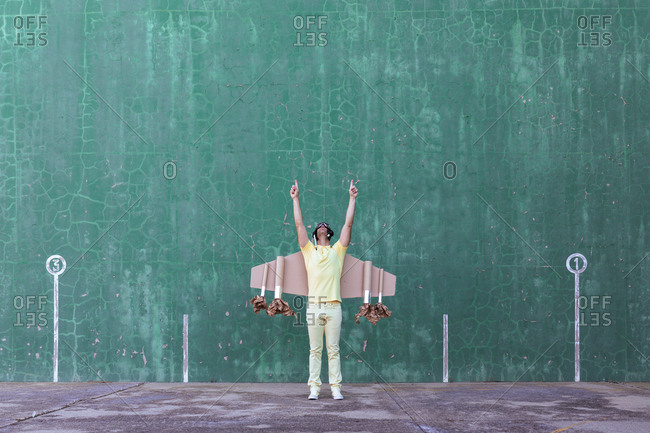 Cheerful male in handmade cardboard wings standing with raised arms and looking up while dreaming about achieving success