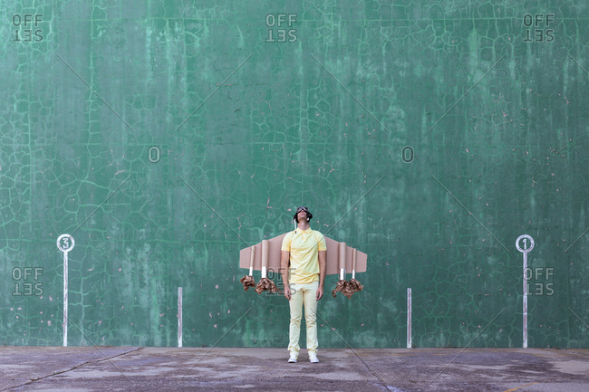 Male in handmade cardboard wings standing looking up while dreaming about achieving success