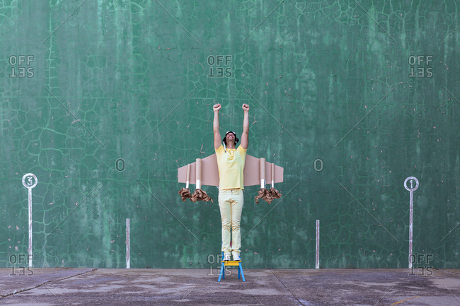 Cheerful male in handmade cardboard wings standing in small chair with raised arms and looking up while dreaming about achieving success