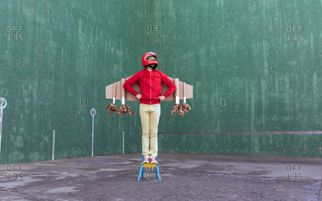 Unrecognizable playful kid wearing handmade carton rocket wings and helmet standing on chair while pretending being astronaut