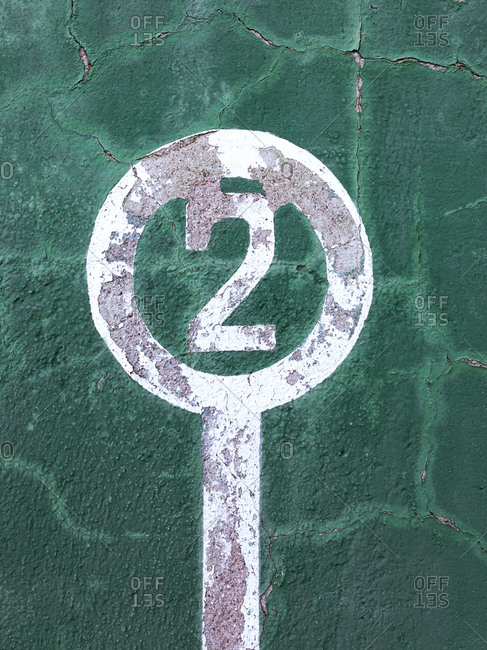 Weathered green wall with peeling paint and number two showing concept of winner