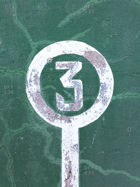 Weathered green wall with peeling paint and number three showing concept of winner
