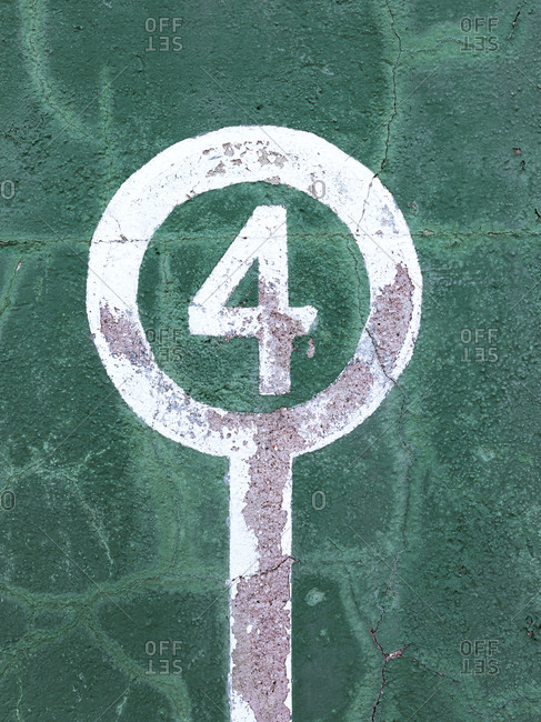 Weathered green wall with peeling paint and number four showing concept of winner