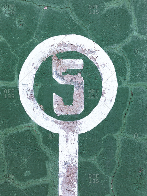 Weathered green wall with peeling paint and number five showing concept of winner