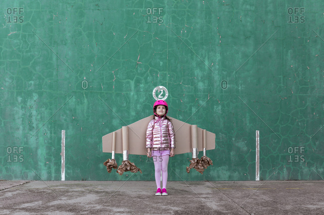 Cute girl in pilot helmet and handmade creative carton wings standing on street on green background looking up