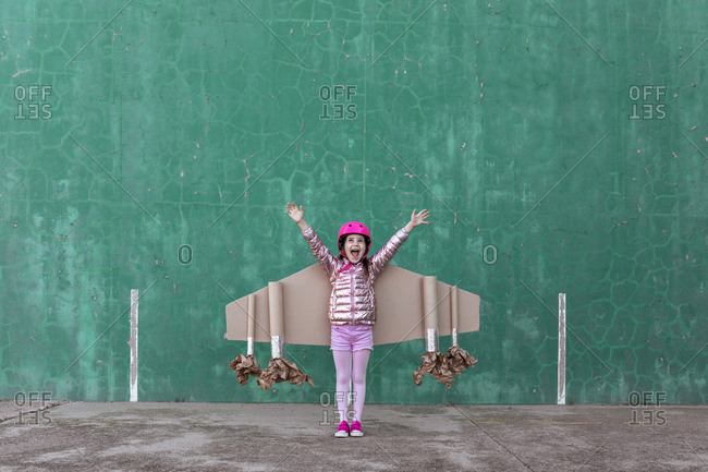 Cute girl in pilot helmet and handmade creative carton wings standing on street with raised arms looking up