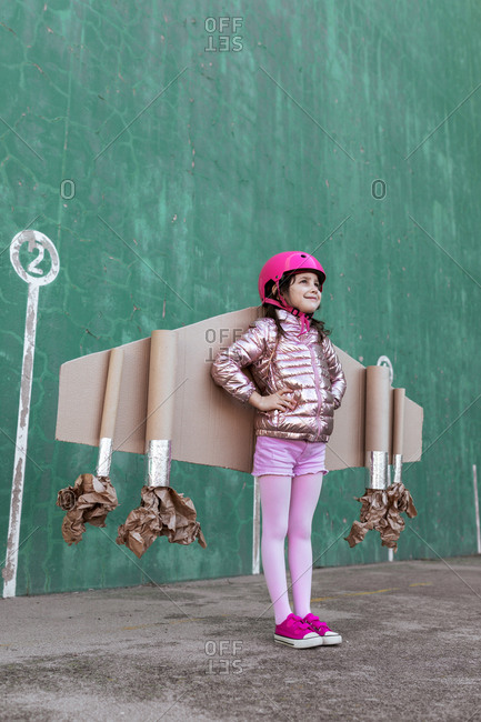 From below side view of cute girl in pilot helmet and handmade creative carton wings standing on street on green background looking away