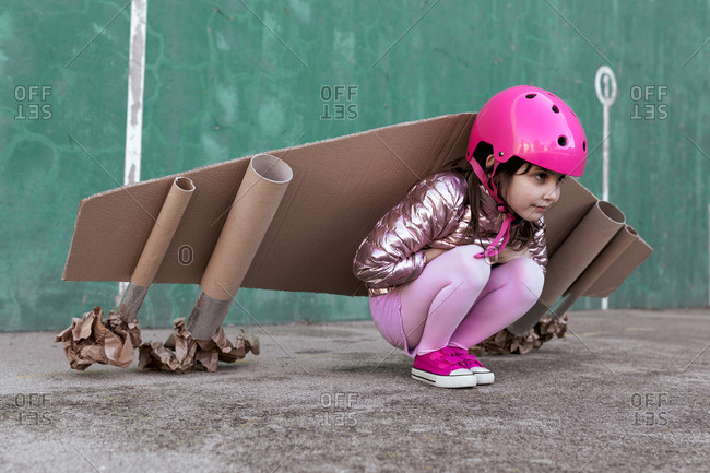 Side view of adorable little girl in cardboard plane wings and protective helmet sitting on street and looking away