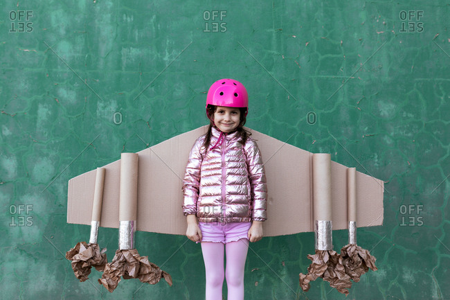 Cute girl in pilot helmet and handmade creative carton wings standing on street on green background looking at camera