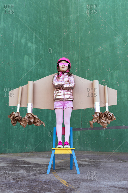 Serious little girl in cardboard plane wings and helmet with funky sunglasses standing on chair on green background
