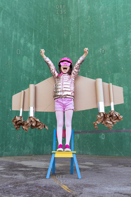 Positive girl in cardboard plane wings and helmet standing on chair with fists up while celebrating achievement and screaming on green background