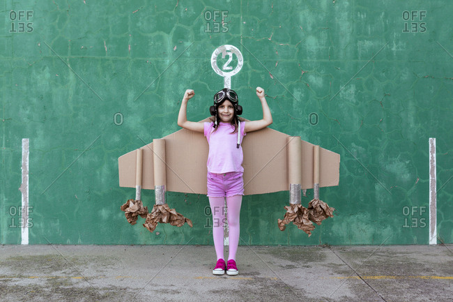 Cute girl in pilot helmet and handmade creative carton wings standing on street with raised arms and showing strength