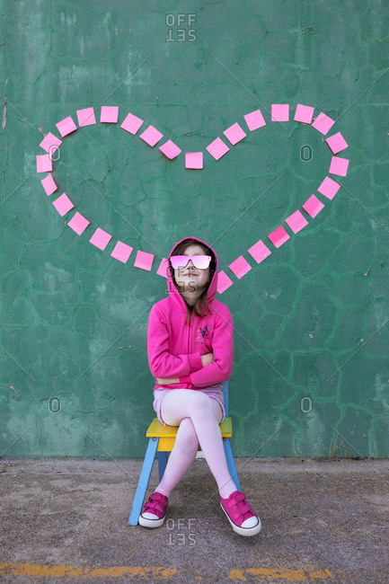 Cheerful cool little girl wearing stylish pink clothes and sunglasses sitting on chair near wall with heart made of sticky notes