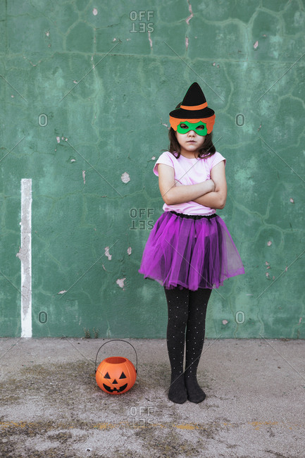 Calm child wearing creative costume of witch standing on street near orange jack o lantern and looking at camera at Halloween