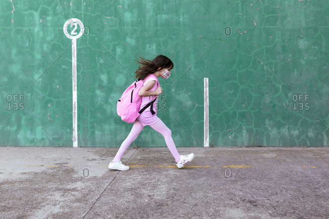 Side view of schoolgirl with rucksack and in protective mask walking along street during coronavirus epidemic