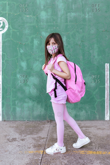 Side view of schoolgirl with rucksack and in protective mask standing on the street during coronavirus epidemic